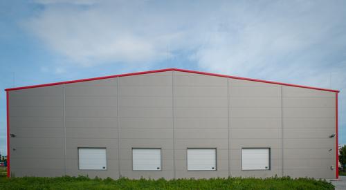 Szürke raktárépület hátsó fala, 4 raktárajtóval