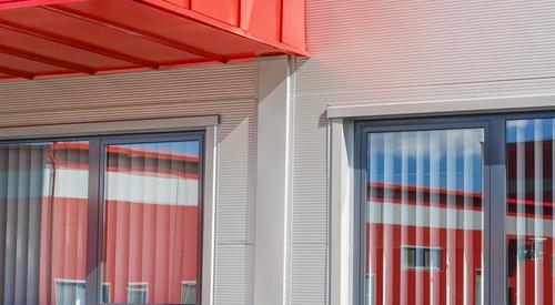 Hell irodai ablakai a szürke panelekben