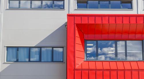 közeli kép az irodai ablakokról (szürke és piros szendvicspanelben)
