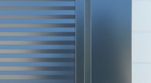 Elburkolás egy fekete szendvicspanel épület sarkán
