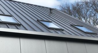 Beépített Velux tetőablakok egy szürke épületen