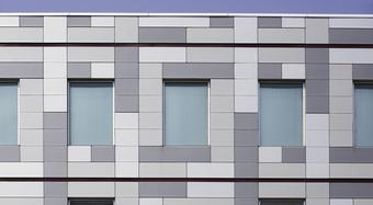 A szürke három árnyalatában pompázó honlokzat ablakokkal
